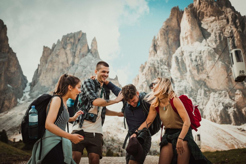 four people laughing together in front of some mountains