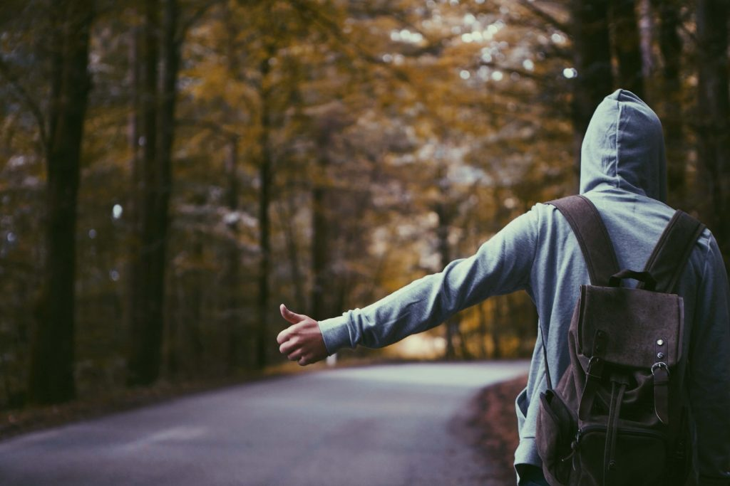 a guy on a street, putting his hand out to find a car to hitchhike