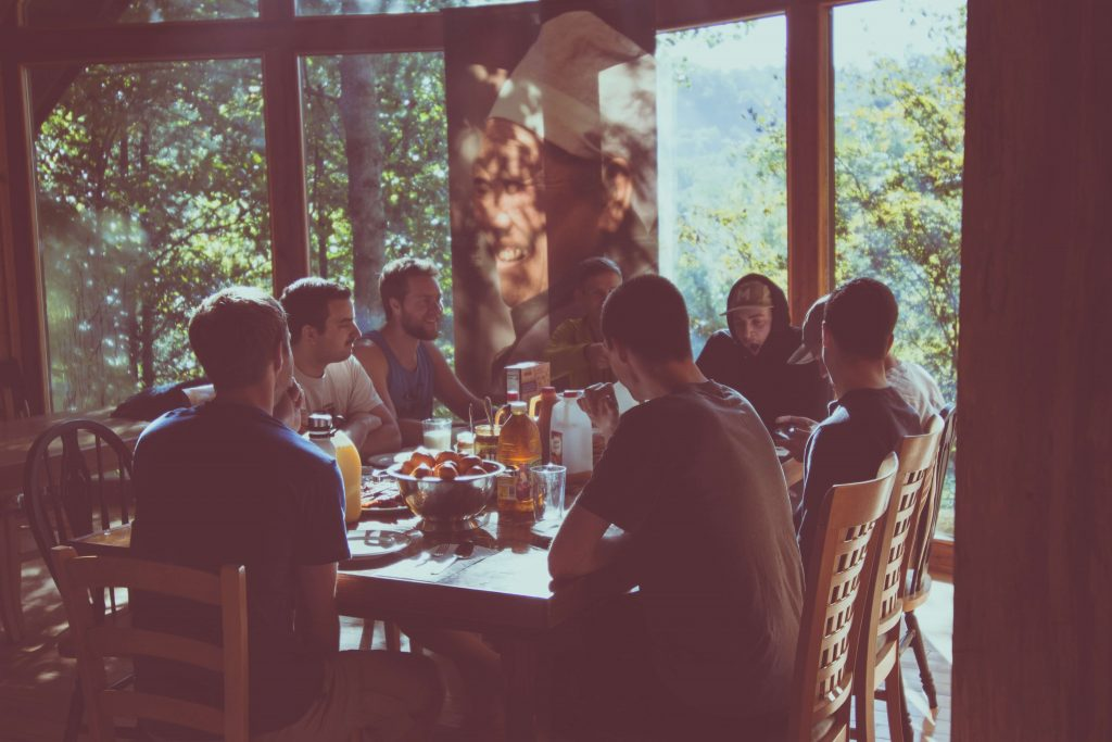 a group of people sitting around a table eating breakfast