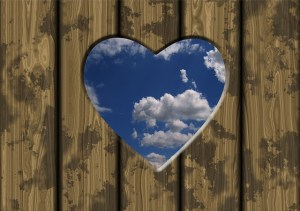 Heart view of clouds through boards