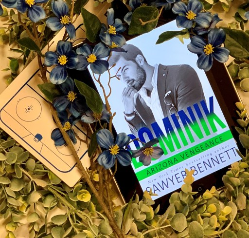 Dominik flatlay with ereader, blue flowers, greenery, and a chart of the ice