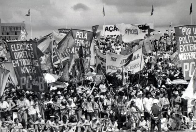A foto mostra uma centena de pessoas segurando cartazes. Está em preto e branco