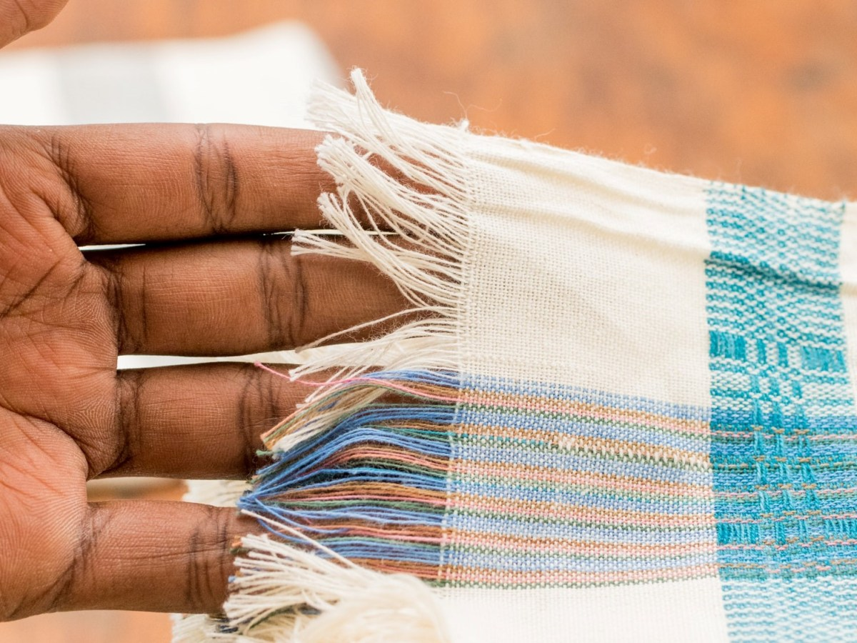 fingers holding threads of a tapesty