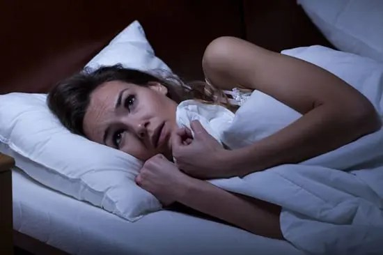 Woman with a phobia staying in bed afraid to leave her room.