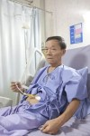 Man patient with gastrostomy receiving tube feeding in hospital bed.