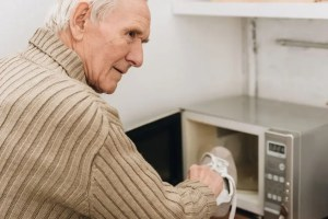 Senior man with dementia disease putting shoe in microwave oven.