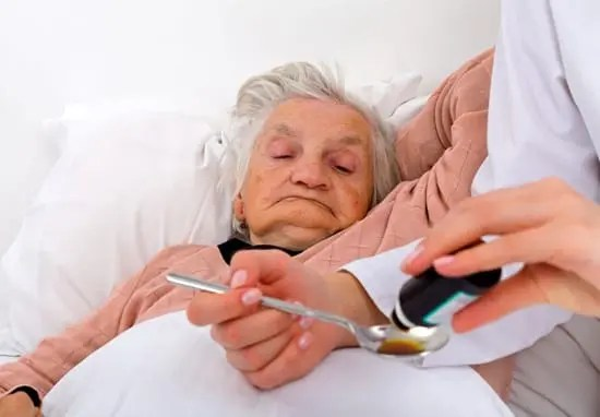 Giving oral medication to elderly woman