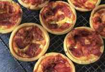 Little pizza quiche sitting on a cooling rack
