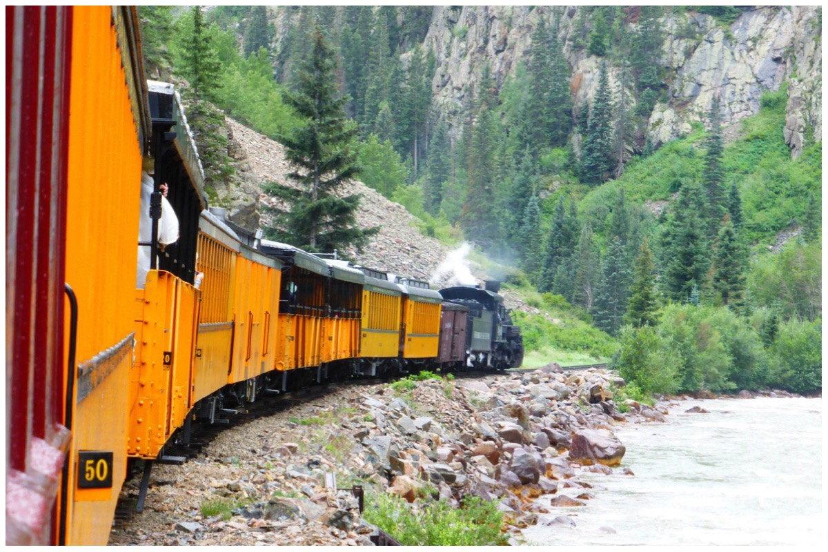 Steam train and carriages traveling along a river in a gorge in the Colorado Mountains
