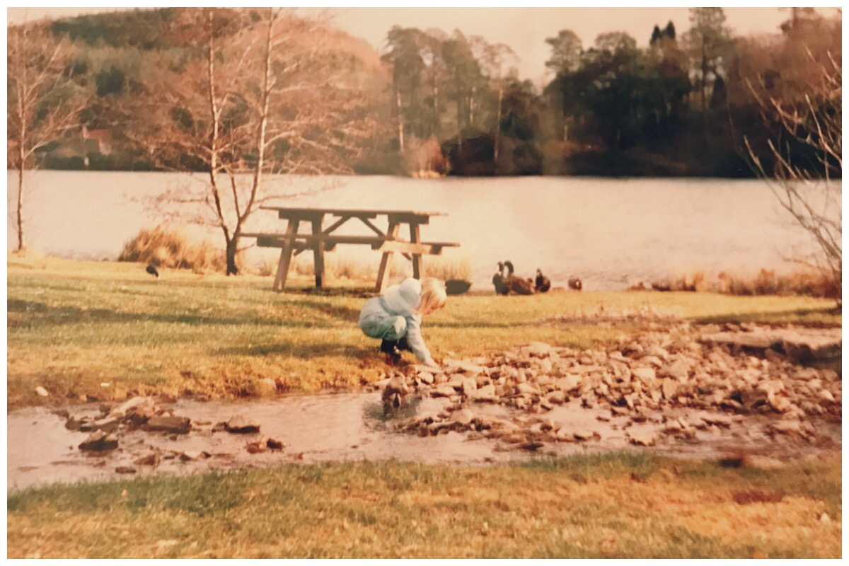 Photo of me as a child at Llyn Mair way back from the 80s. The photo see me standing by the river, the lake in the background and ducks waddling