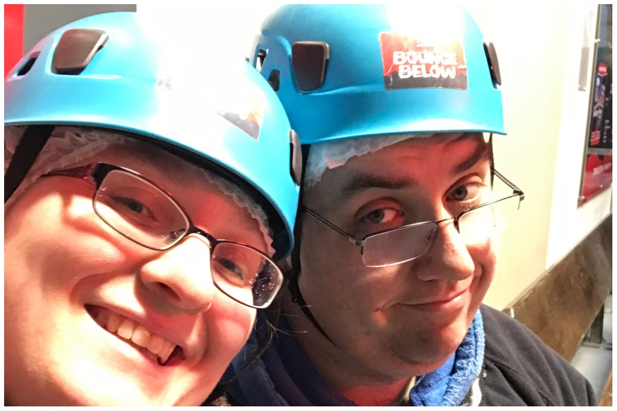 A photo of me and the husband wearing our hard hats ready to go trampolining underground at Bounce Below Zipworld