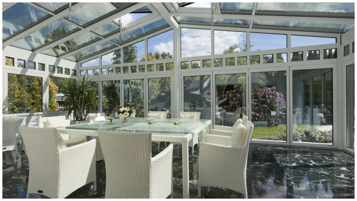 Big windowed conservatory with white rattan furniture