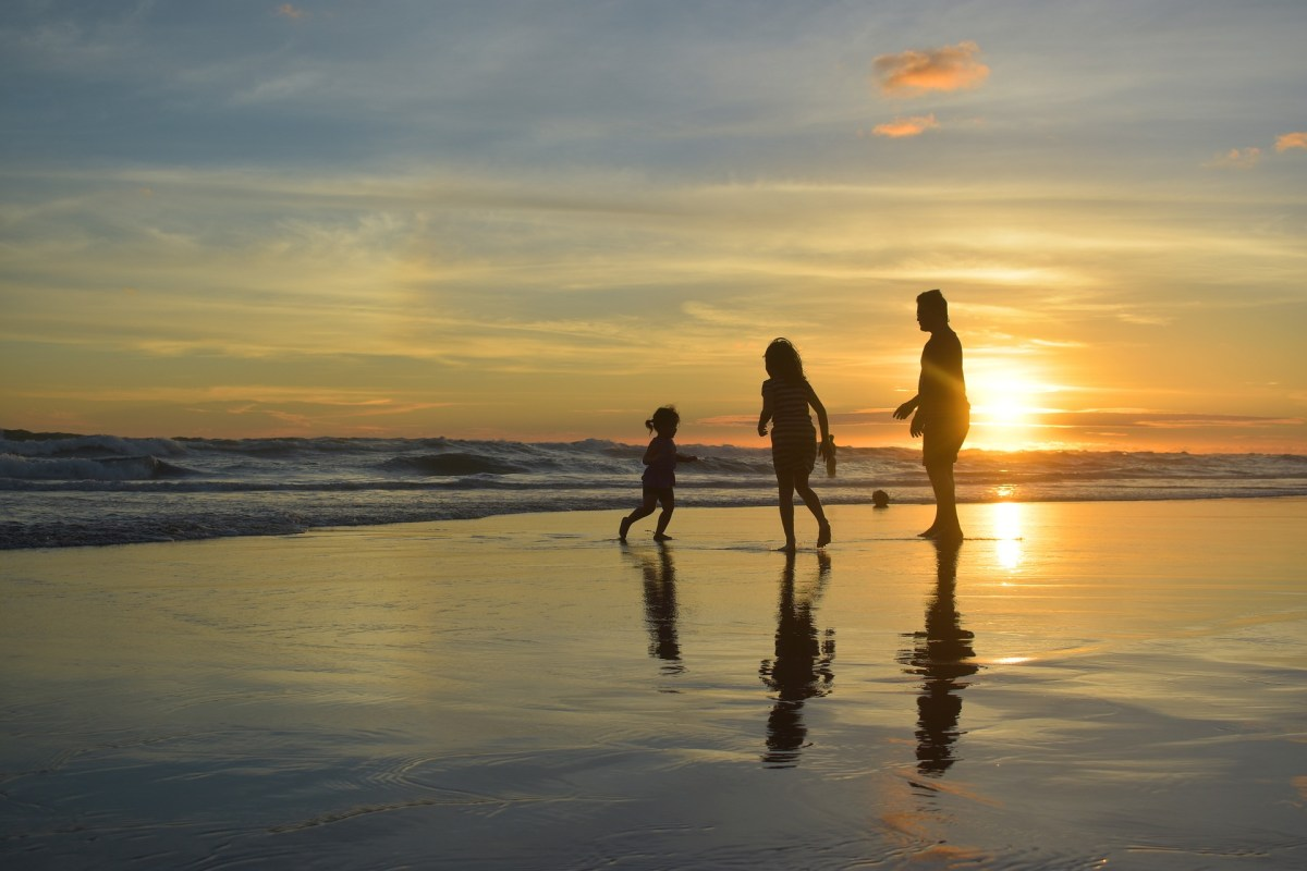 Family silhouette on the beach at sunset