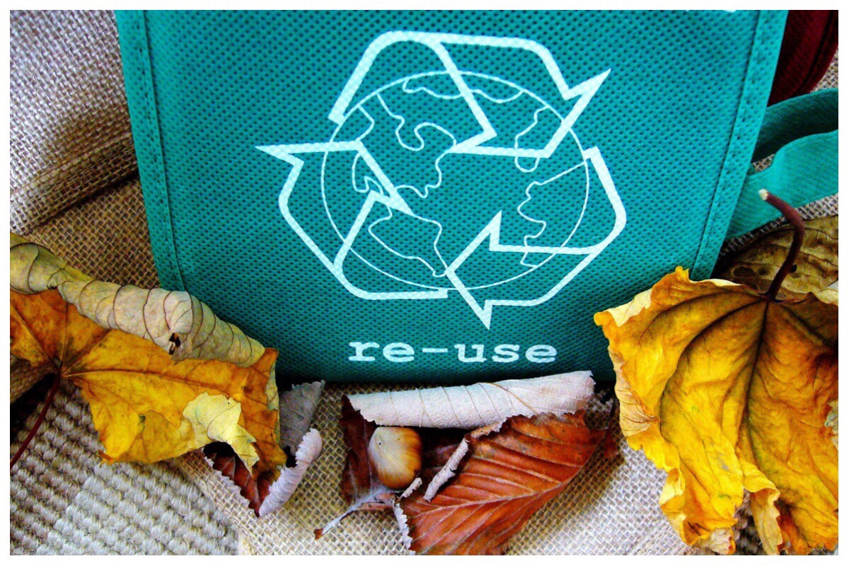 Green fabric bag with the words re-use and the recycling symbol on it