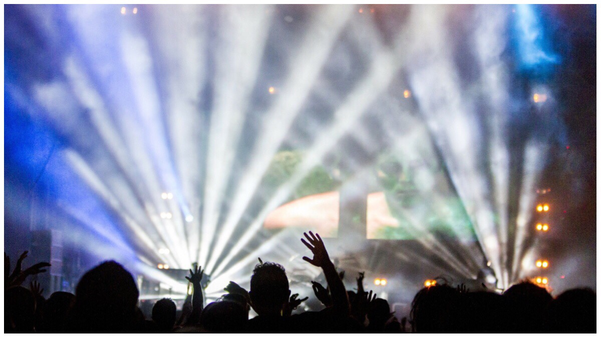 A concert crowd silhoutted against a brightly lit stage