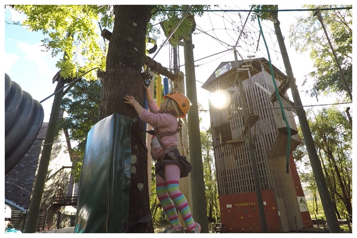 My Little Miss conquering the Low Ropes course - photo shows her on the course with the High Ropes tower in the background and the sun shining through the trees
