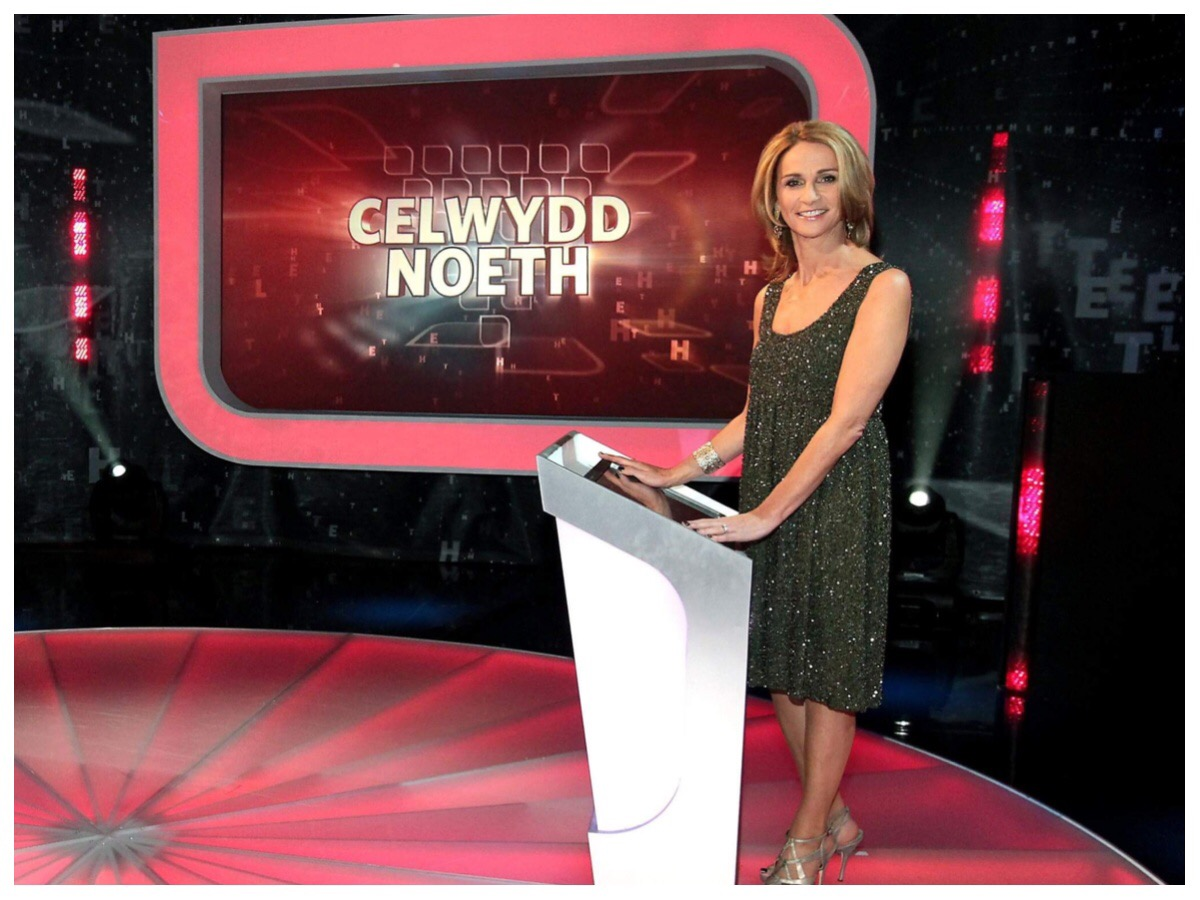 The host Nia stood at the podium in front of the Celwydd Noeth screen