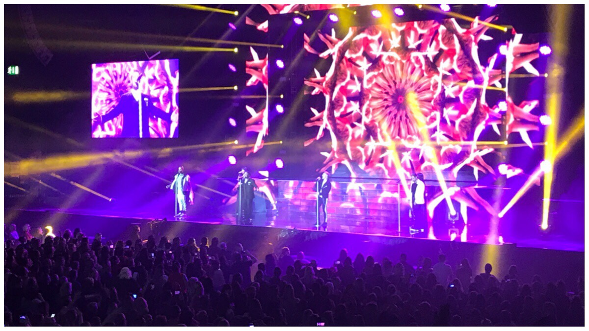 Boyzone on stage at Birmingham arena. The four guys on stage in front of a kaleidoscope of reds and yellow. In the foreground is the crowd in darkness.