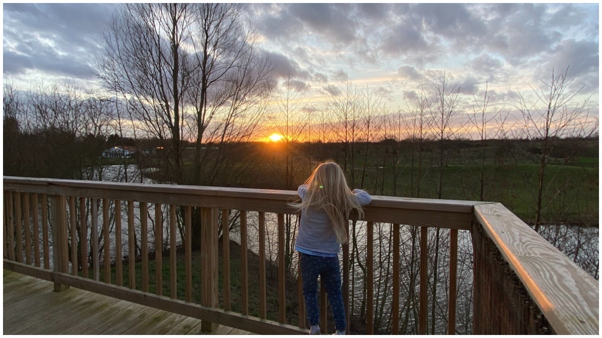 Our 4 year old standing on the decking of our holiday accommodation looking at the sunset. Kings Wood Lodges, Doncaster, Yorkshire