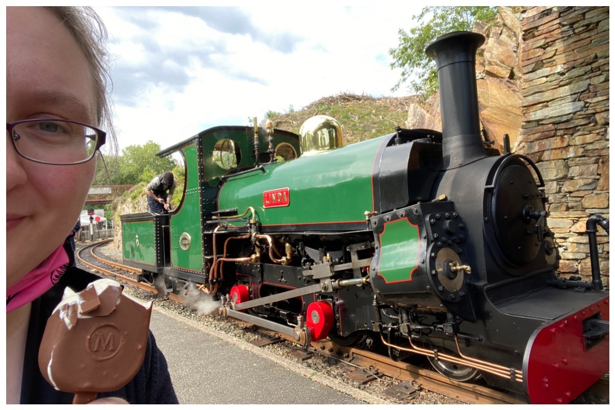 Rebecca eating an ice cream with Linda the green coloured Hunslet engine at Tan Y Bwlch Station on the Ffestiniog Railway
