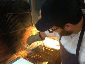 Suarez pours sizzlin' coals on the grill (Photo: Natalie Rinn)