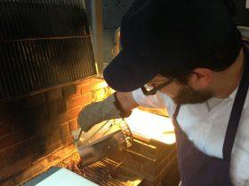 Suarez pours sizzlin' coals on the grill (Photo: Natalie Rinn)