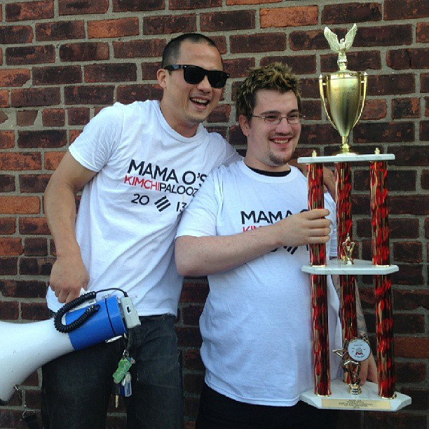 A previous kimchi eating contest winner, with trophy (image via Mama O
