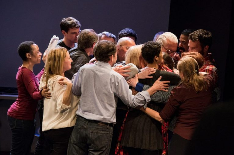 Standing group of people huddled in a group hug
