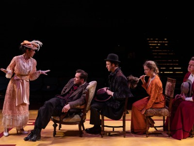 5 Actors on Stage, One standing the other sitting in single file row in chairs. Victorian Dress Costumes