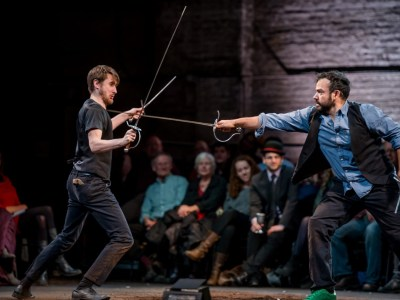 Two actors sword fighting with audience in the background