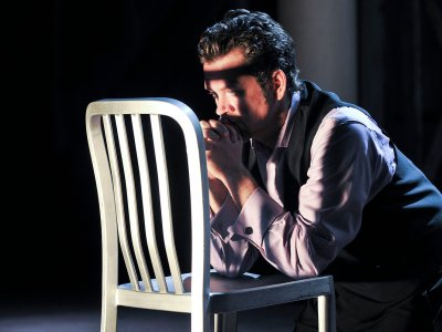 actor on stage kneeling at a chair in prayer pose