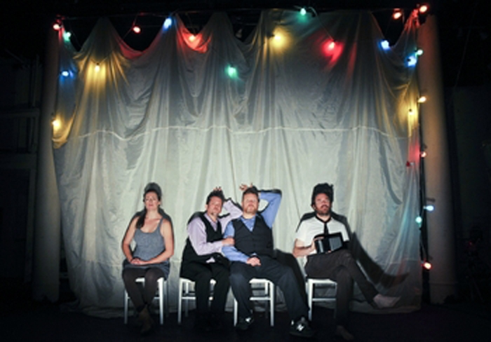 Four actors on a stage sitting in chairs with christmas lights above them