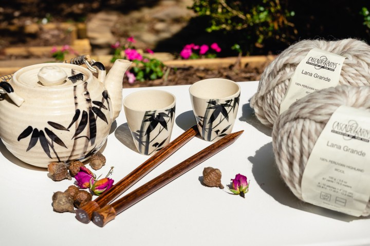 Learn to knit.  100% Peruvian Wool and Knitting Needles in a scene with teapot and cups.  Yarn and needles used to knit a scarf.