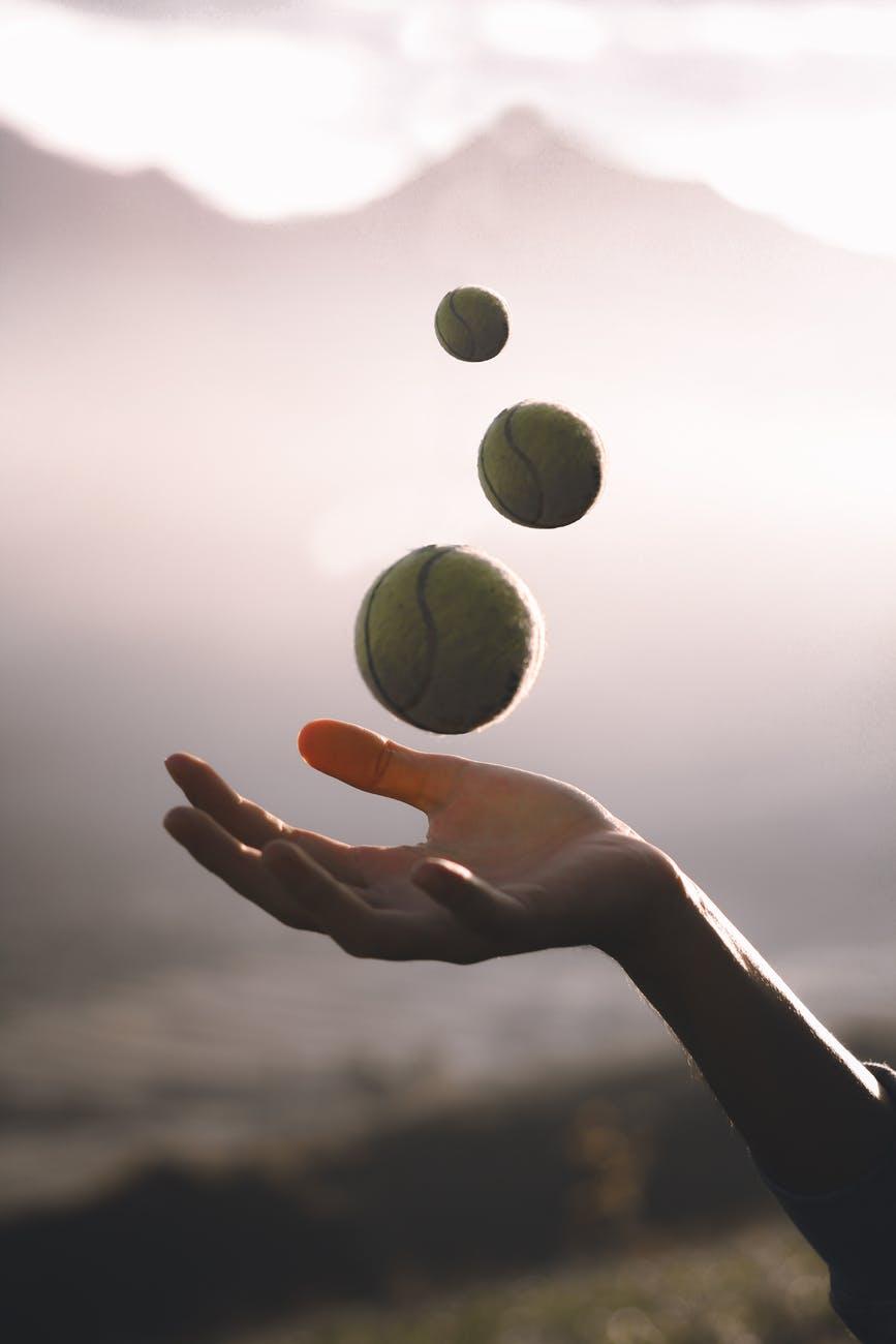 crop sportswoman juggling tennis balls on meadow