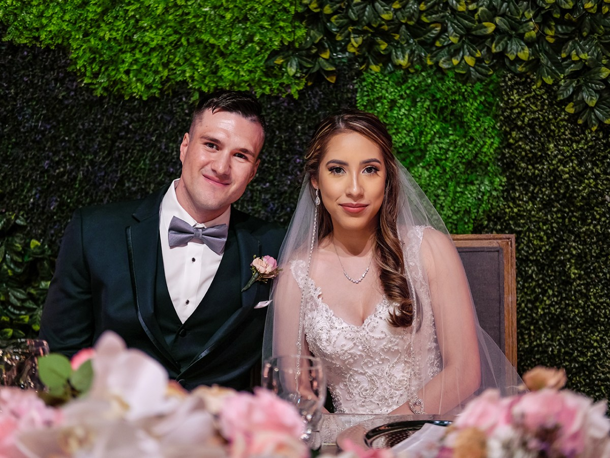 Seated at their table at their beautiful wedding at the Orchidee Studio Social Events Venue off 10th st in McAllen Tx is a newly wed couple. They smile into the camera in front of a wall of greenery. Their table is decorated by pink flowers.