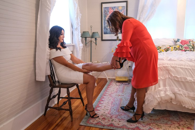 mother helping bride put on wedding shoes the bryan house
