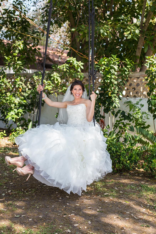 Bride swinging on metal swing smiling for camera in McAllen, Texas.
