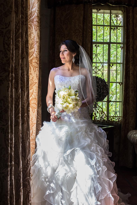 Bride looking out of window at Quinta Mazatlan in McAllen, Texas.