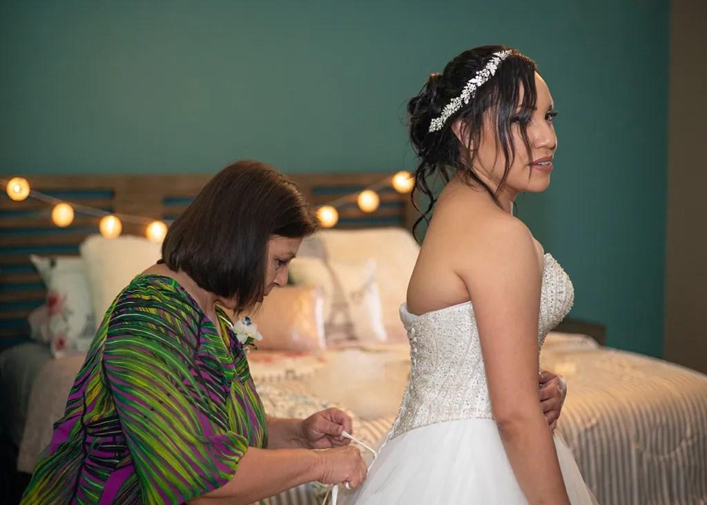 mother helping bride tie her dress