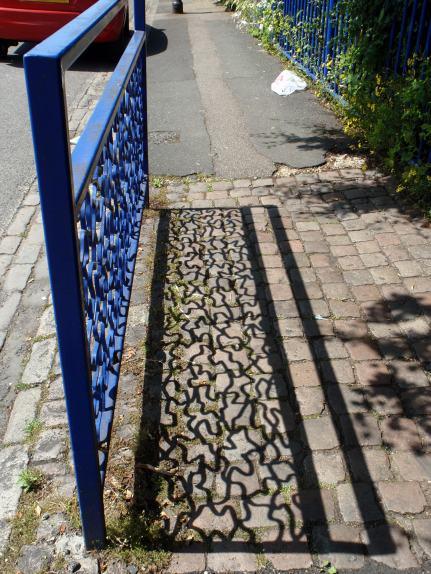 Shadow of iron work commuity garden peckham