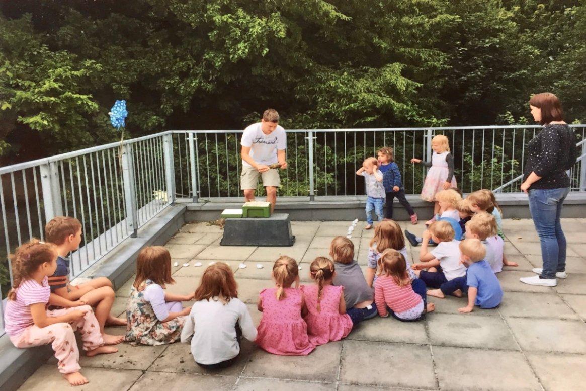 Imker Felix Mrowka zeigt Kinder ein Bienenvolk