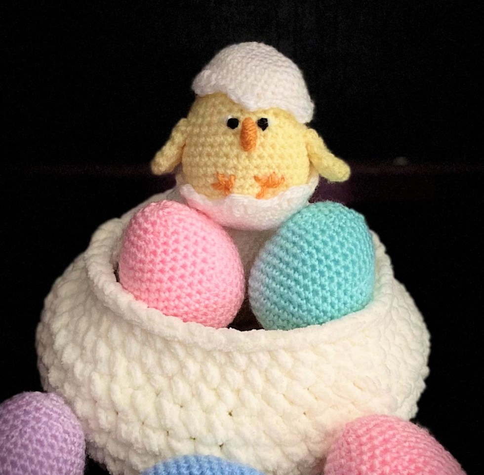 baby chick in shell on top of easter eggs
