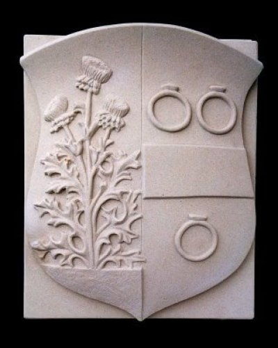 A coat of arms stone with family crest in Bentheimer sandstone. The weapon contains three rings, a bar and a three-flowered thistle