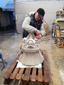 de beeldhouwer bindt het beeldhouwwerk vast op de pallet