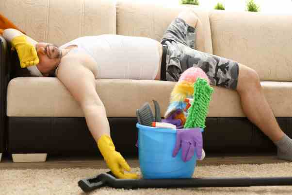Man asleep on couch wearing clean gloves and cleaning supplies near.
