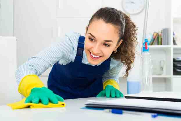 professional cleaner in working overall  dusting in modern office