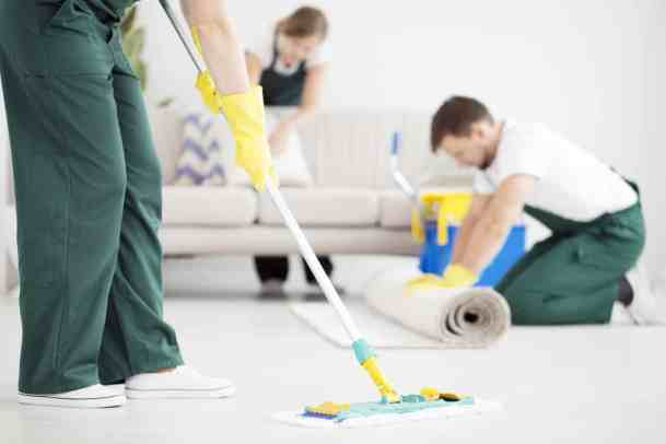 Cleaning crew cleaning the floor using a mop in bright flat