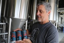 Brewery founder Brian Purcell holds one of the first cans of A Night on Ponce.