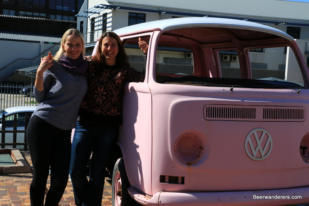 girls by a pink VW