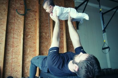 man using a baby as a weight to get a in quick workout at home